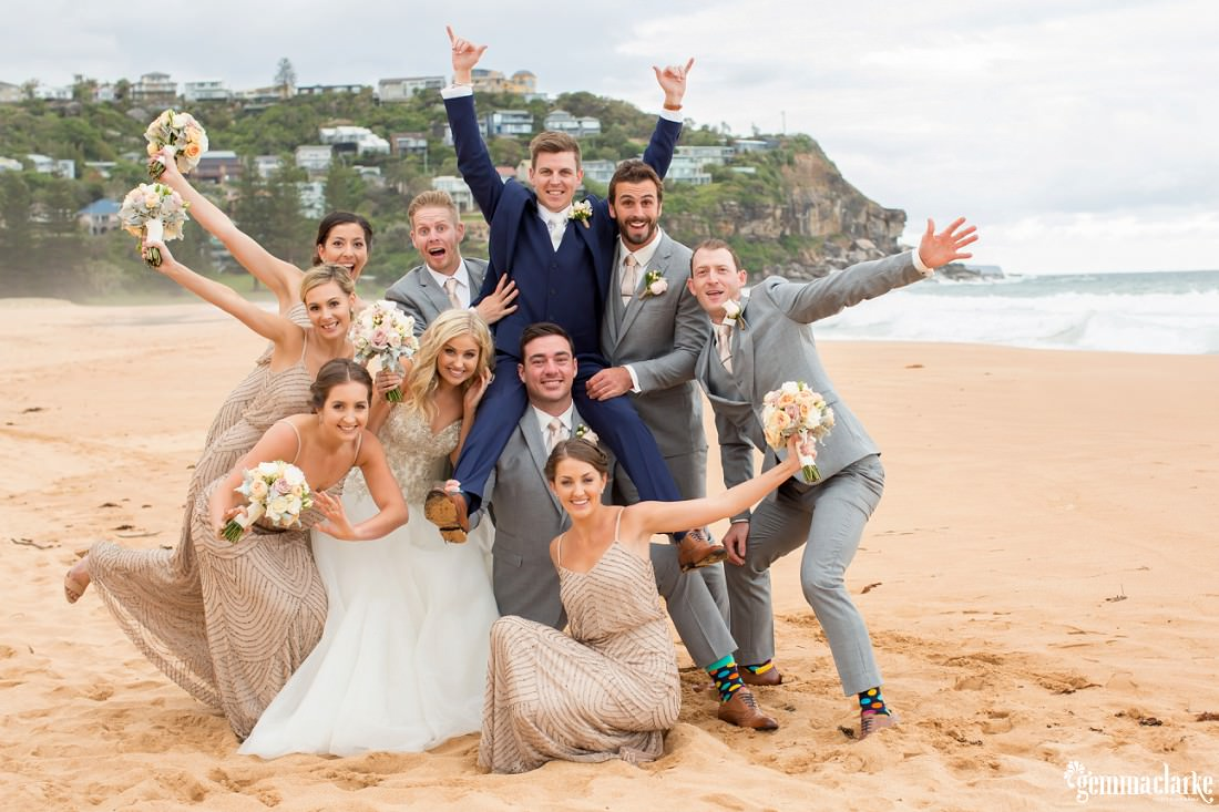 A wedding party posing with hands in the air on Whale Beach, the groom sitting on the shoulders of his best man