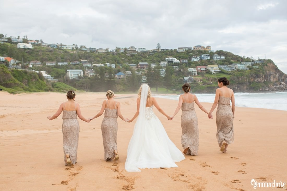 A bride and her bridesmaids walking down a beach holding hands