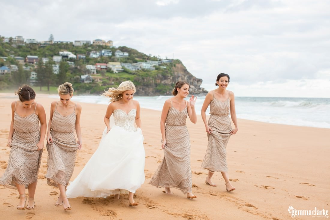 A bride and her bridesmaids walking down a beach together