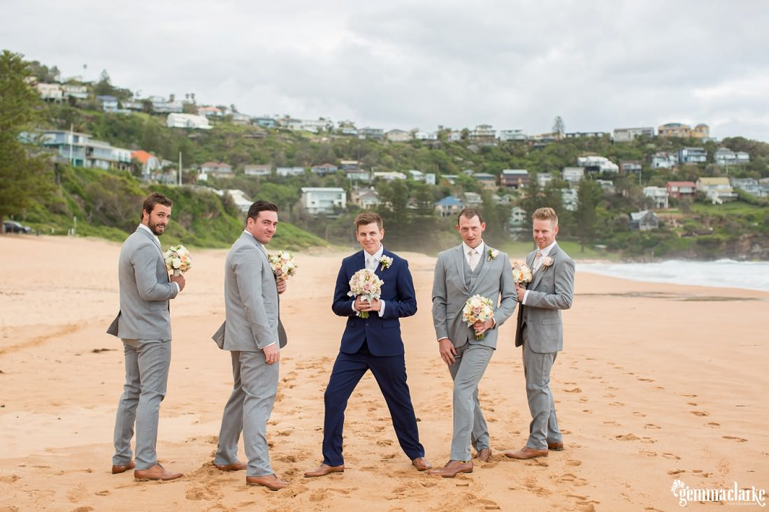 A groom and his groomsmen posing on a beach while holding floral bouquets