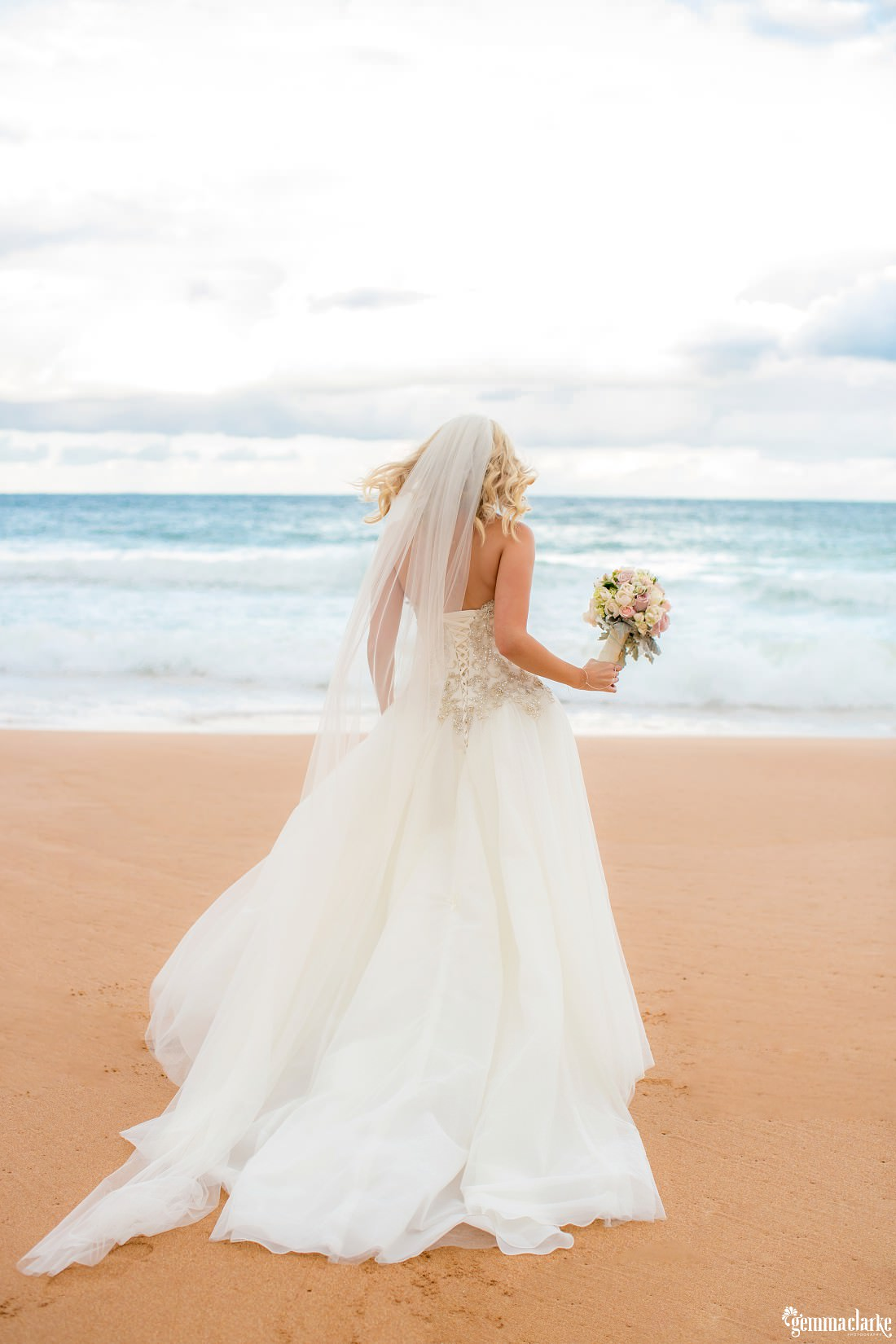 A bride holding her bouquet and standing on the beach, looking toward the ocean