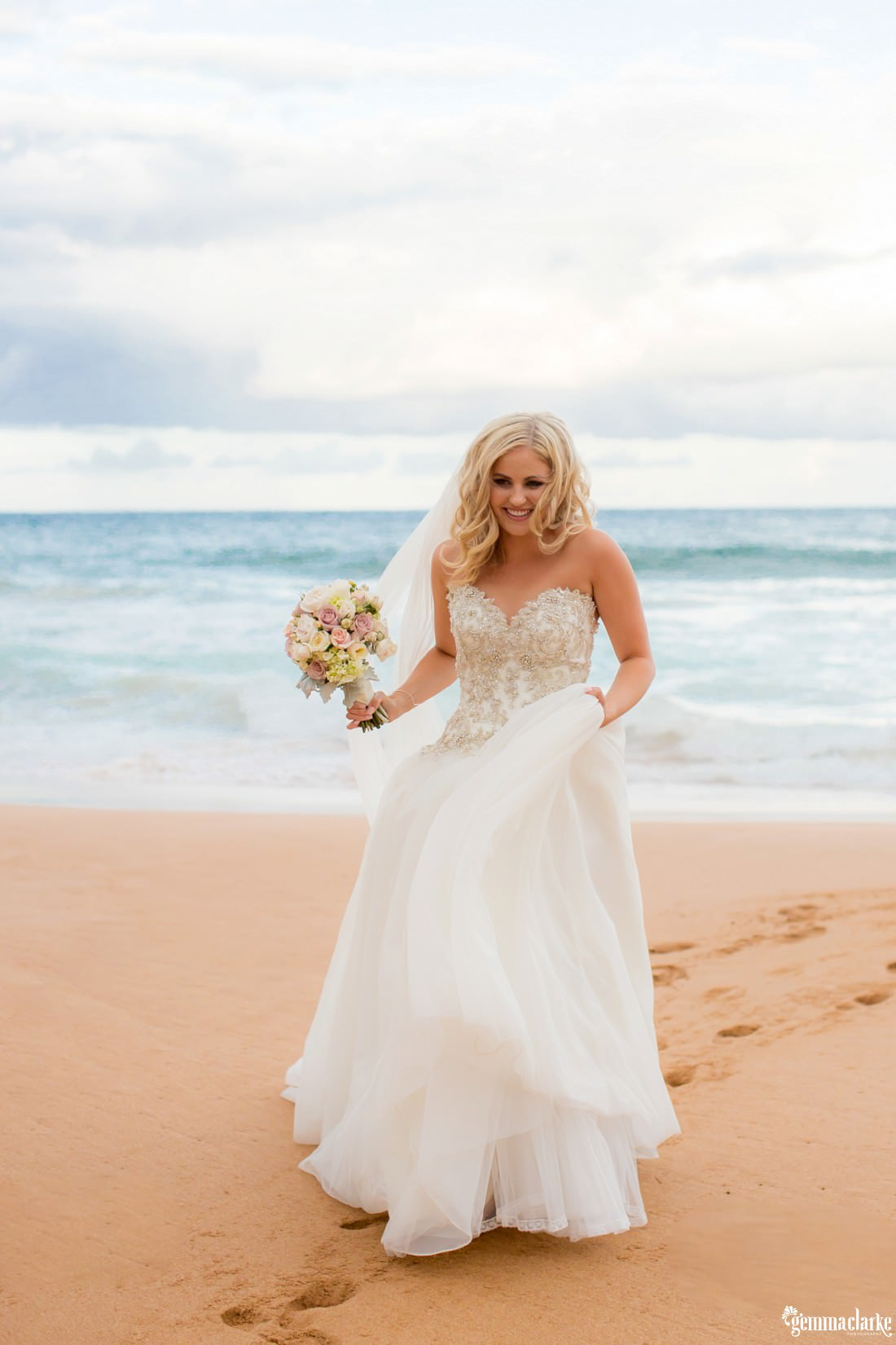 A bride smiling and holding a bouquet, standing on a beach as waves crash in the background