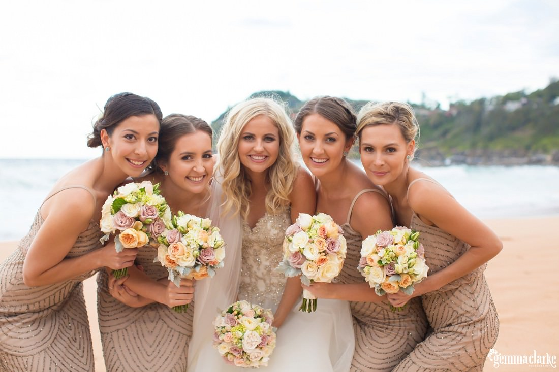 A smiling bride and her bridesmaids lean in close and hold up their bouquets