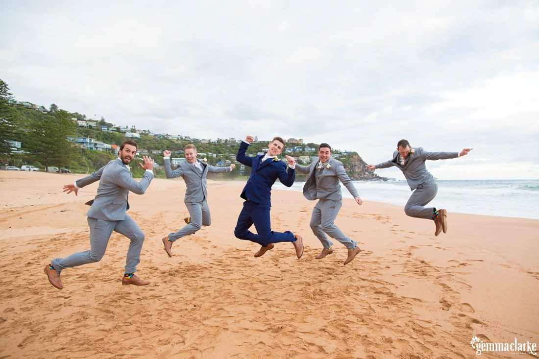 A groom and his groomsmen jumping in the air and posing on a beach