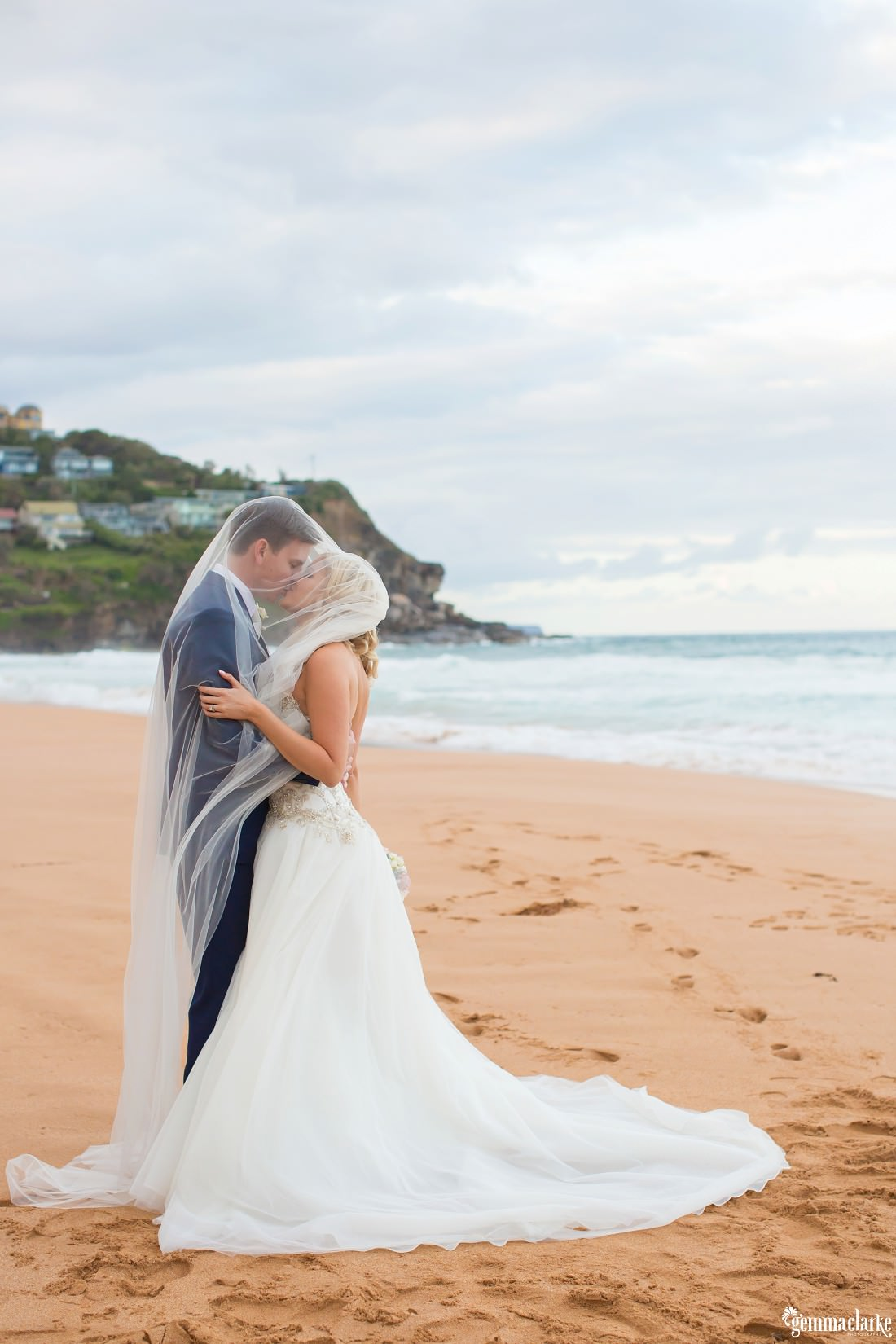 A bride and groom underneath the bride's veil sharing a kiss on Whale Beach