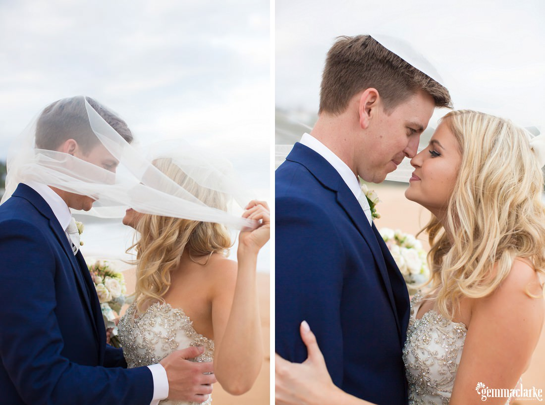 A bride and groom underneath the bride's veil smiling and sharing an eskimo kiss