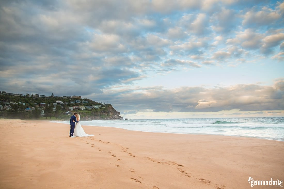A bride and groom sharing a kiss on a beach under the clouds