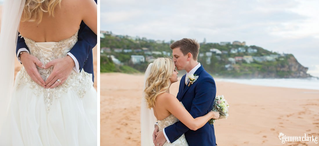 A groom kisses his bride on the forehead as they embrace on the beach