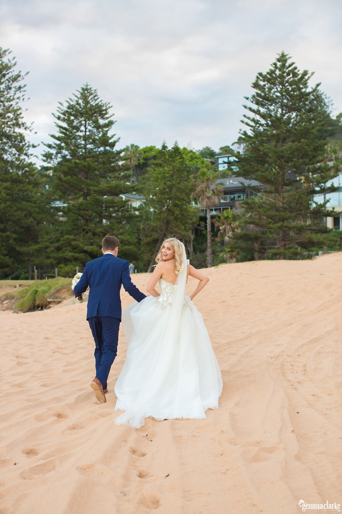 A bride smiles and looks back over her shoulder as she and her groom walk along a beach