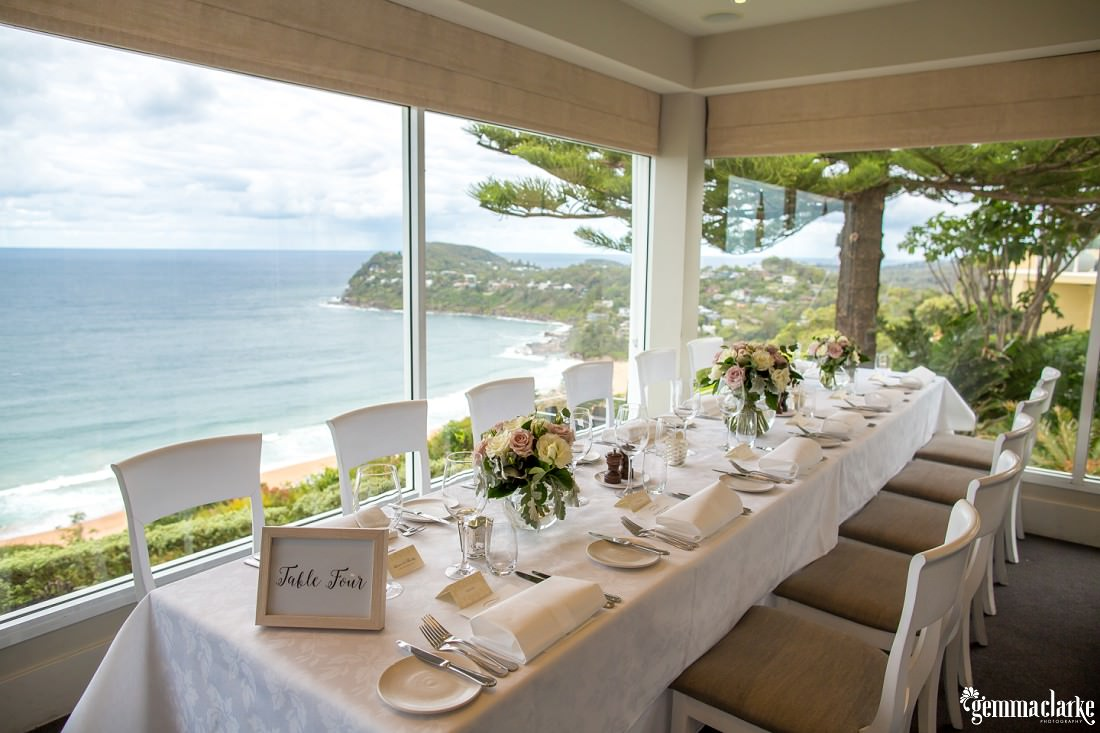 A table at a wedding reception near a window overlooking a beach