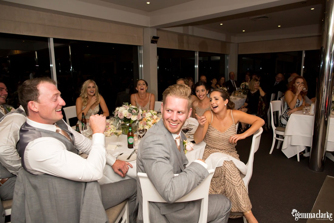 Members of the bridal party laughing and smiling at their table