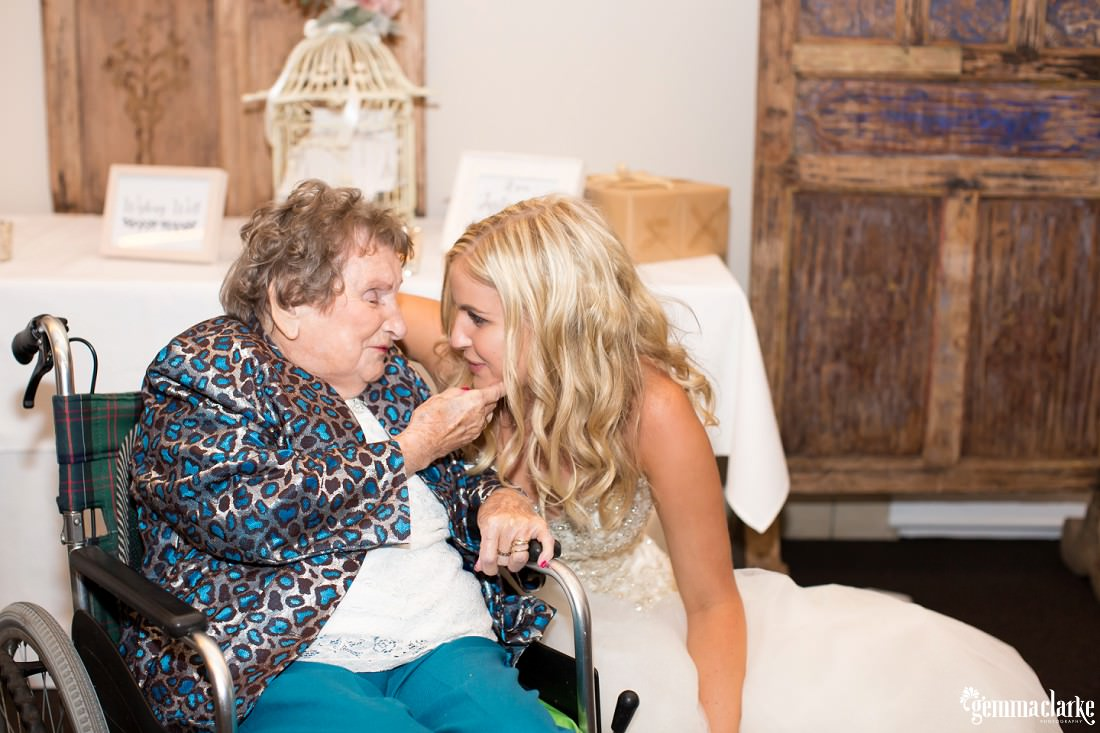 A bride shares a moment with a relative at her wedding reception