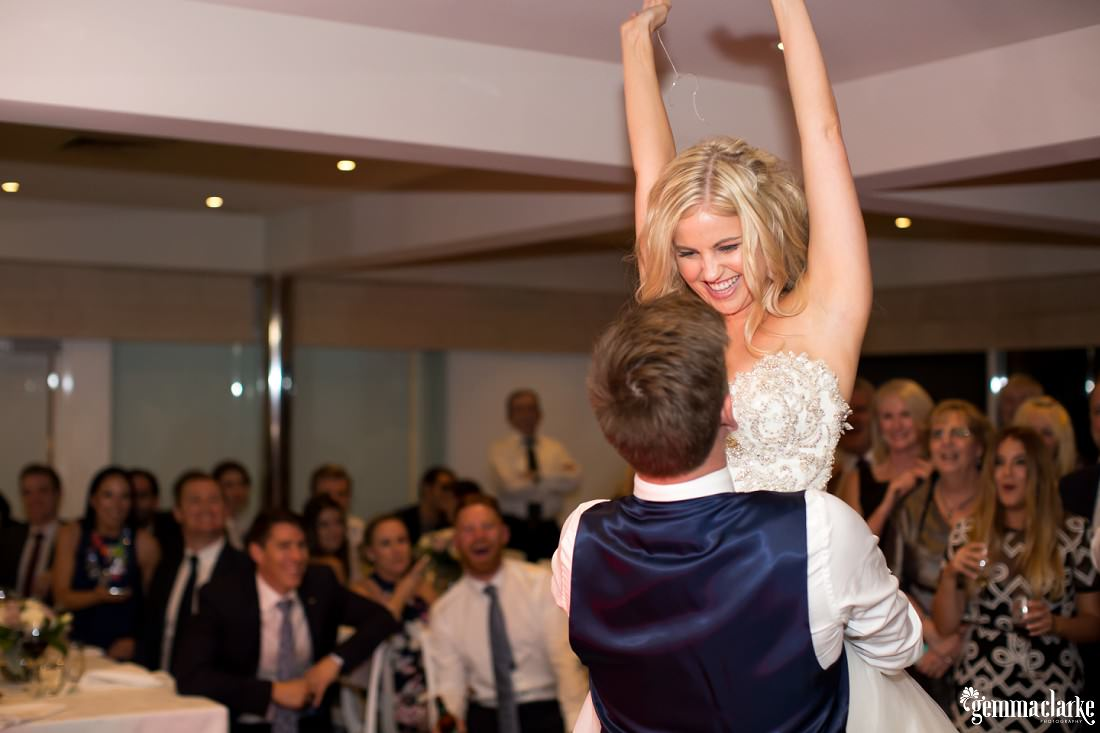 A groom lifts his bride up in their air during their first dance