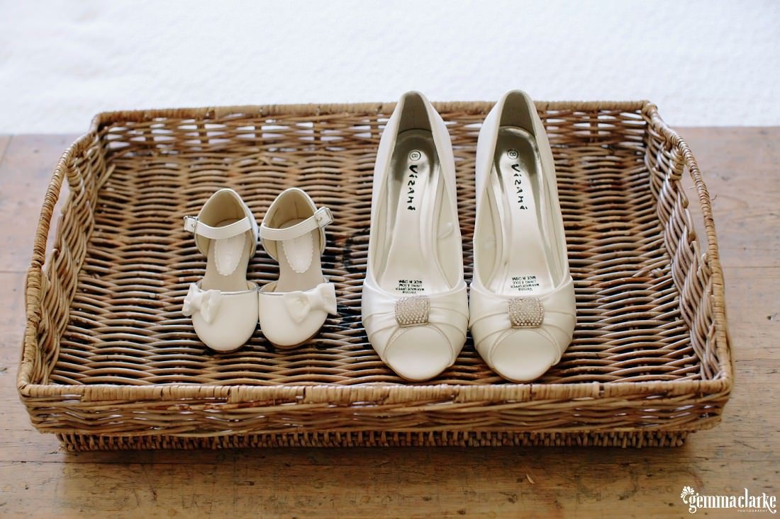 A pair of off-white bridal shoes and a pair of off-white young girl's shoes in a rectangular wicker basket