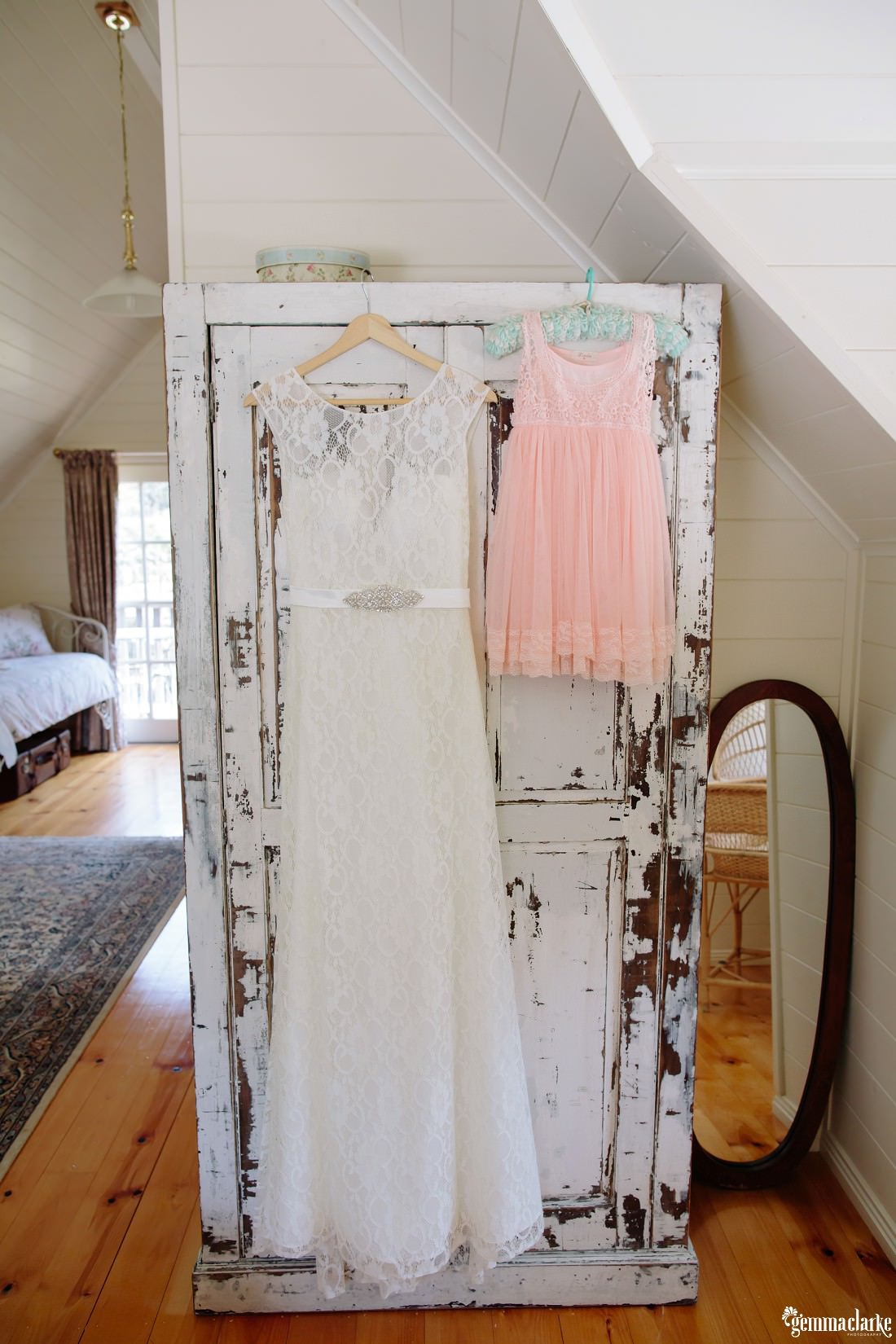 A white bridal gown and light pink flower girl's dress on hangers hanging in front of a white wardrobe