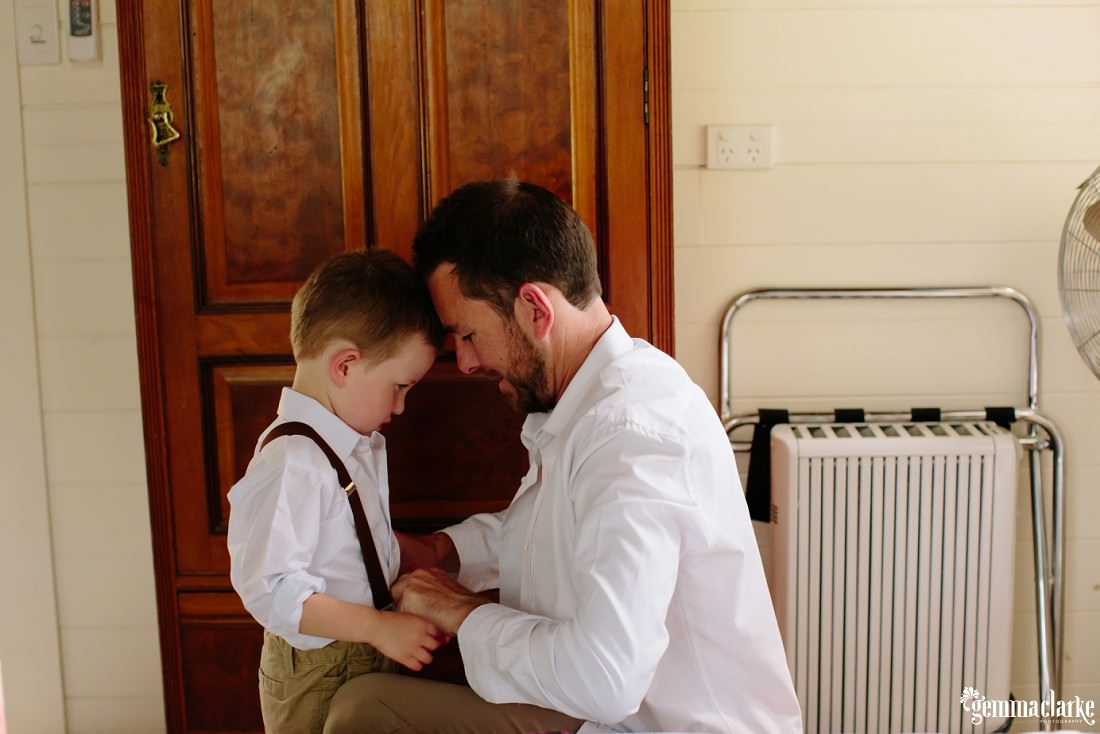 A man helps his young son into his wedding day attire