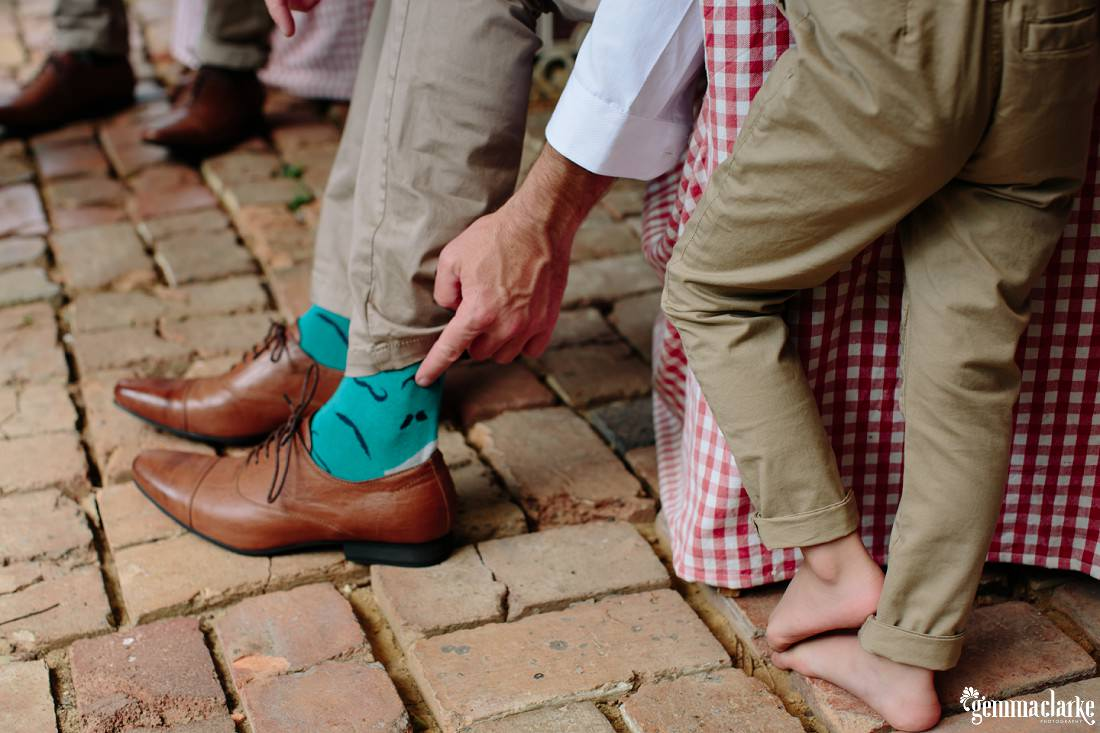 A man points to the moustache design on his socks as his young son stands next to him