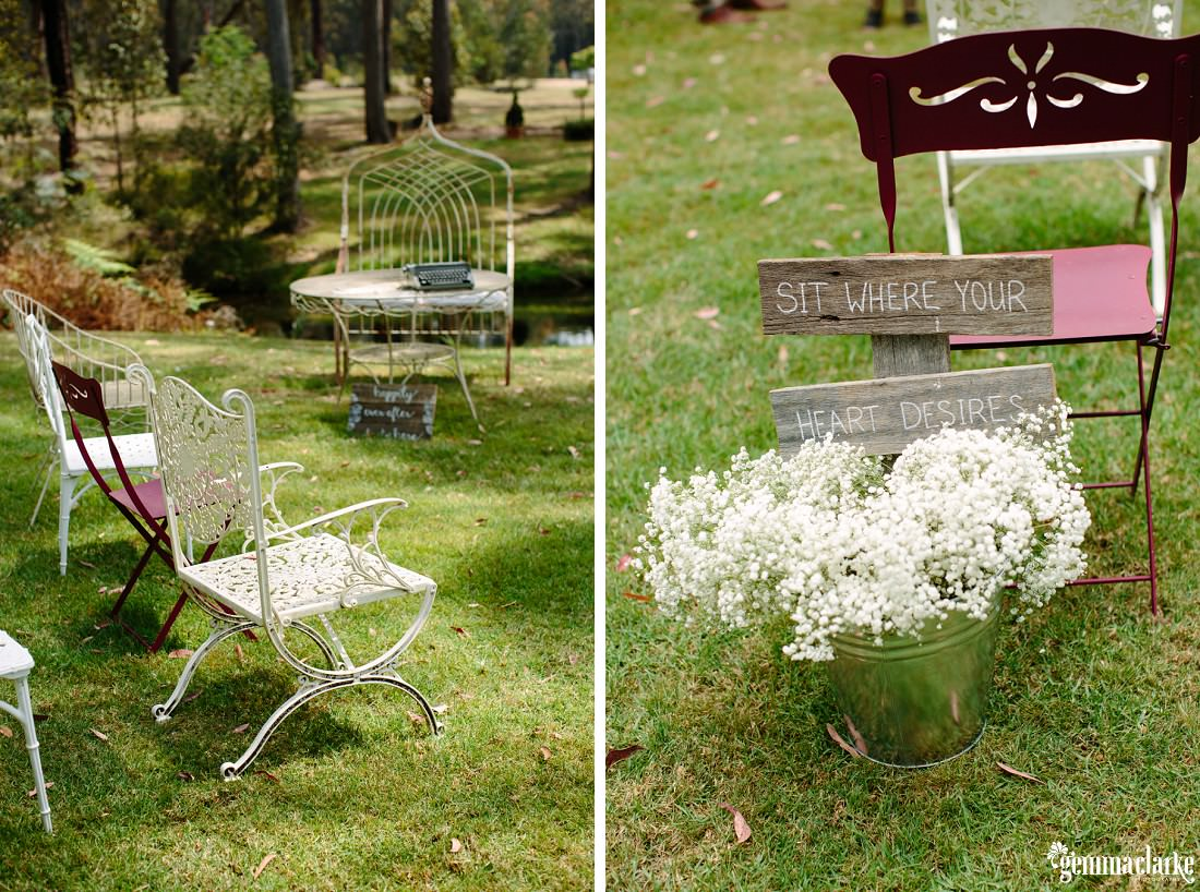 "Mismatched chairs at an outdoor wedding ceremony and a steel bucket of white flowers with a sign that says ""Sit where your heart desires"""
