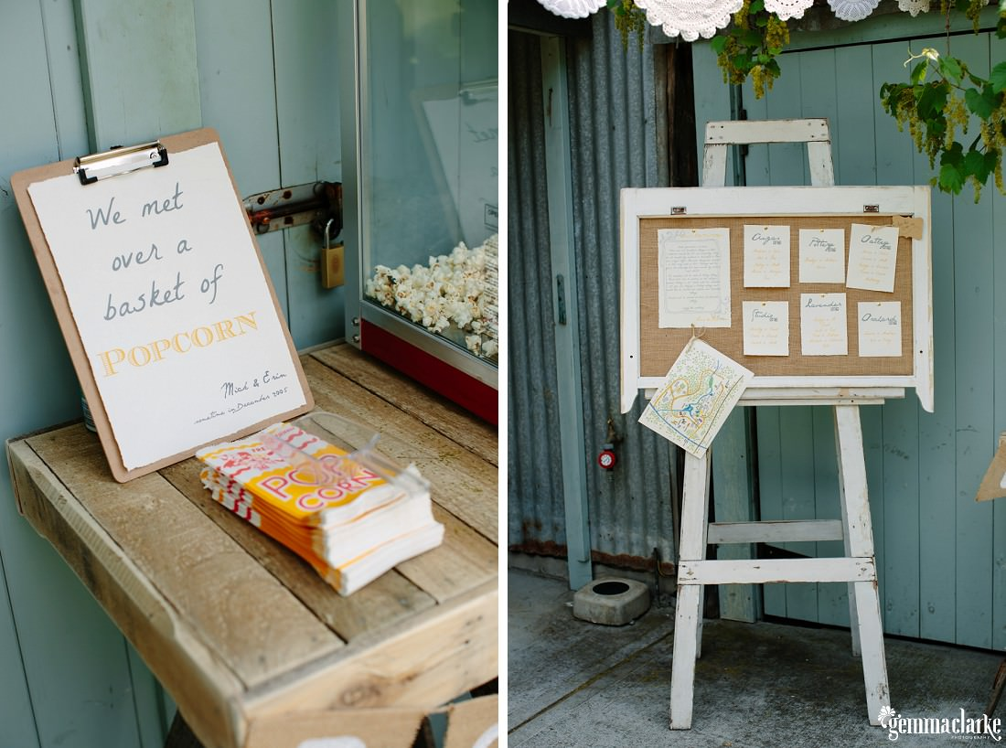 "A sign saying ""We met over a basket of popcorn"" behind popcorn bags and next to a popcorn maker, and an easel with a pinboard mounted on it"