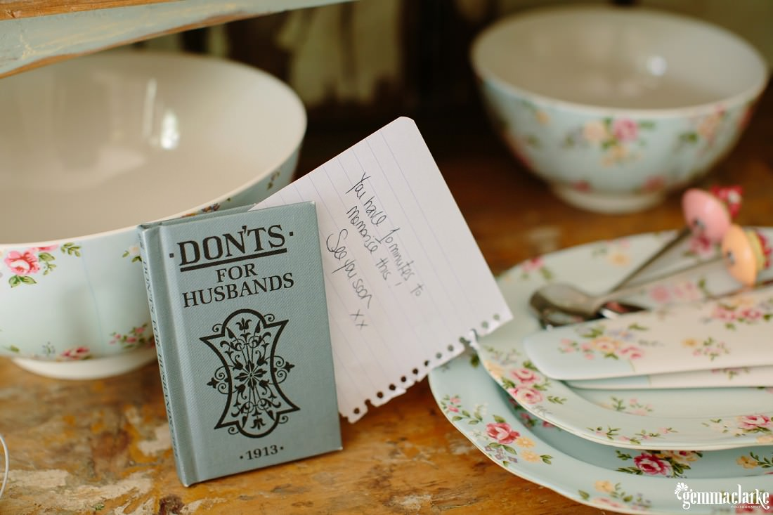 "A small book titled ""Don'ts for husbands"" dated 1913 with some floral tableware"