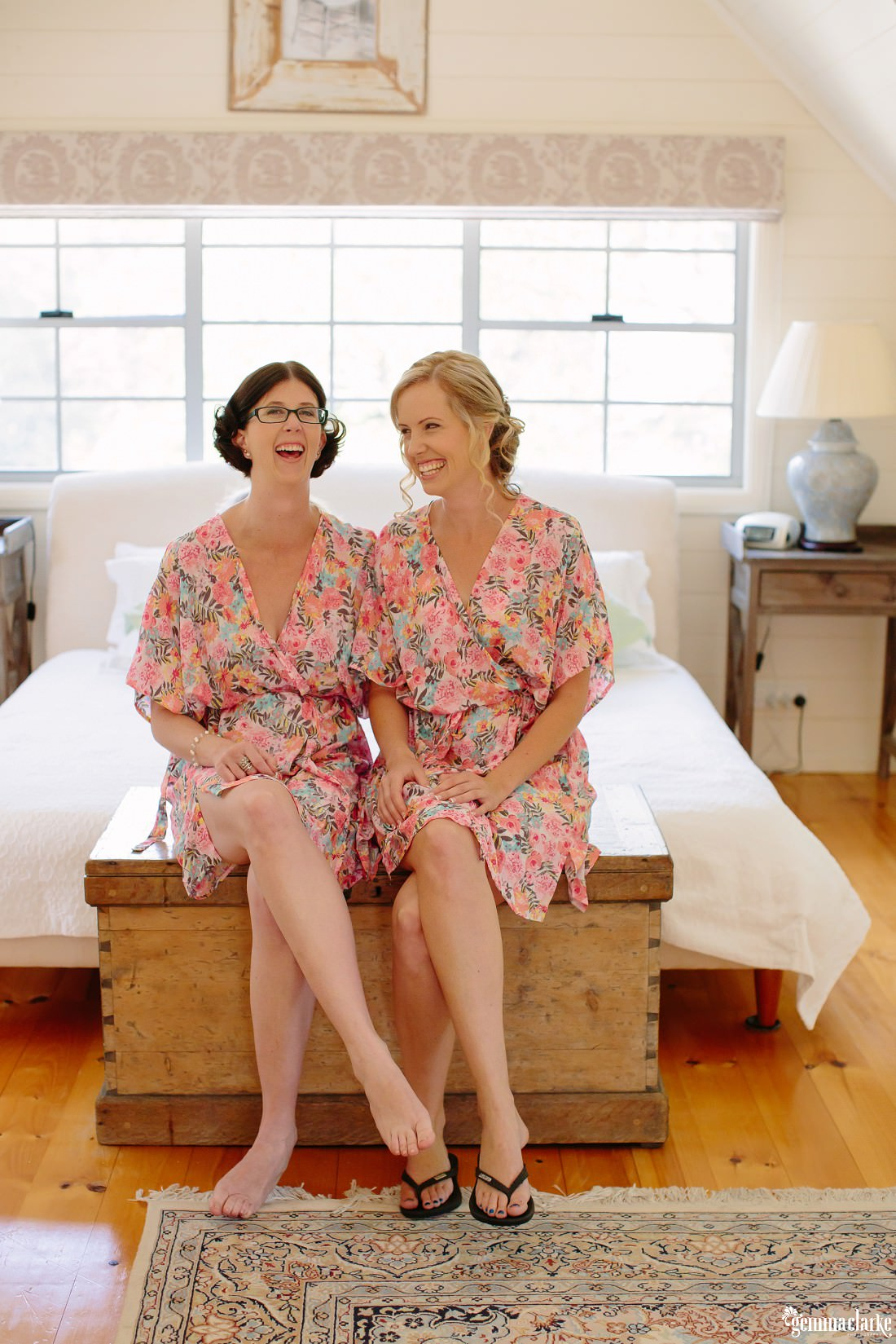 A bride and her maid of honour in matching floral robes sitting and laughing together