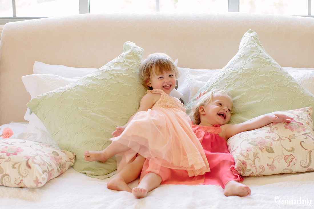 Two smiling young girls laying on some cushions