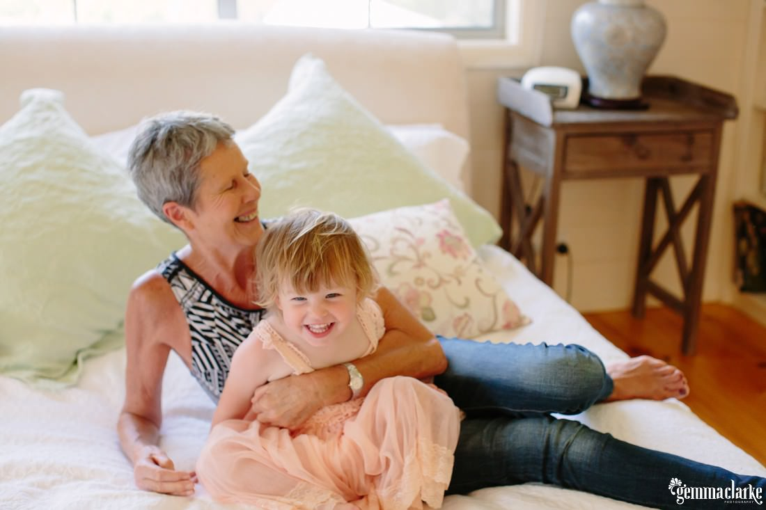 A young girl and her grandmother laughing and sitting on a bed