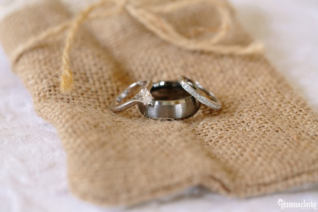 Three white gold rings on a small hessian bag