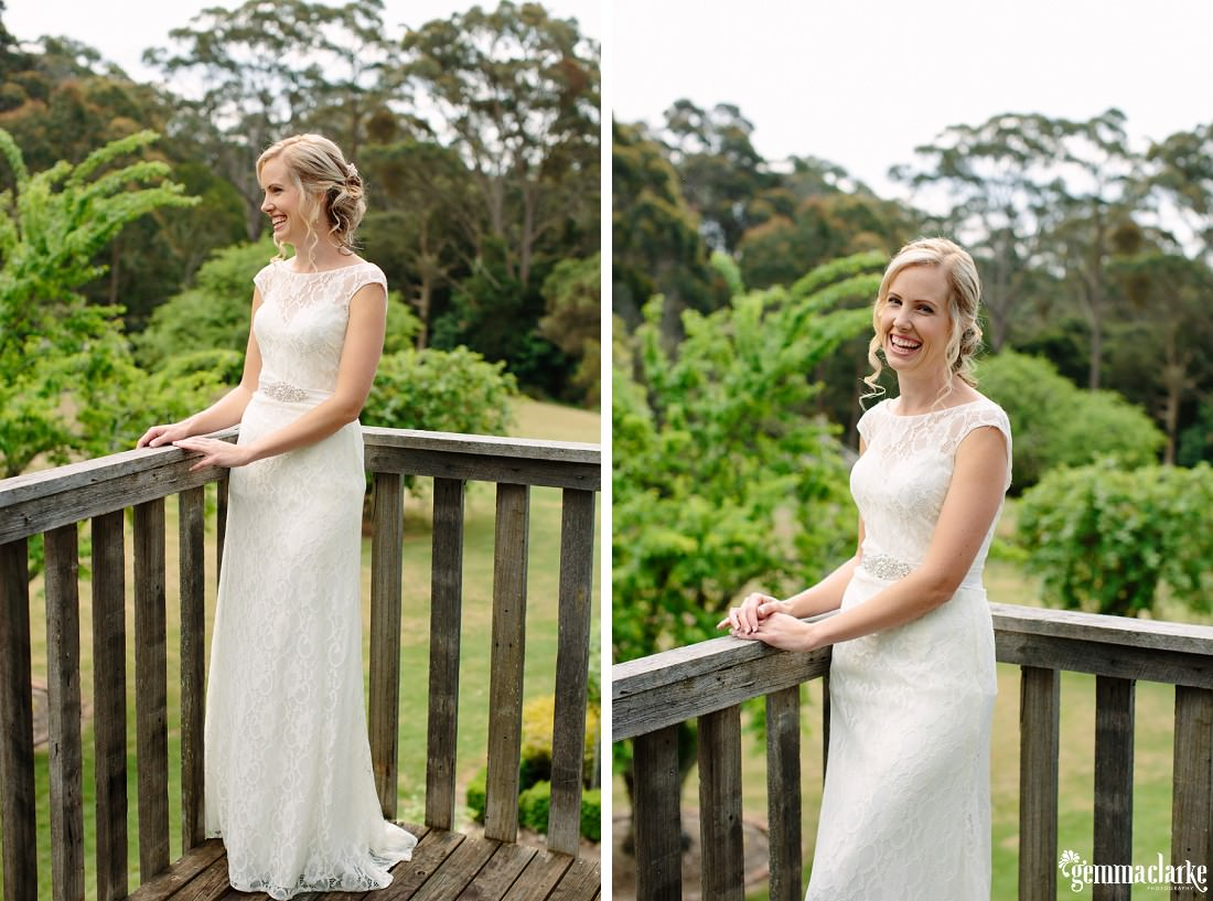 A smiling bride in a white gown standing on a deck and leaning against the railing
