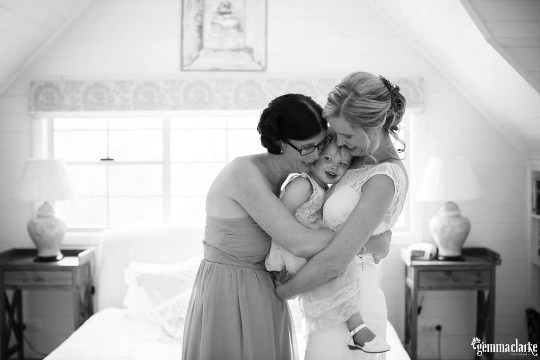 A bride holding her daughter and both being hugged by the maid of honour