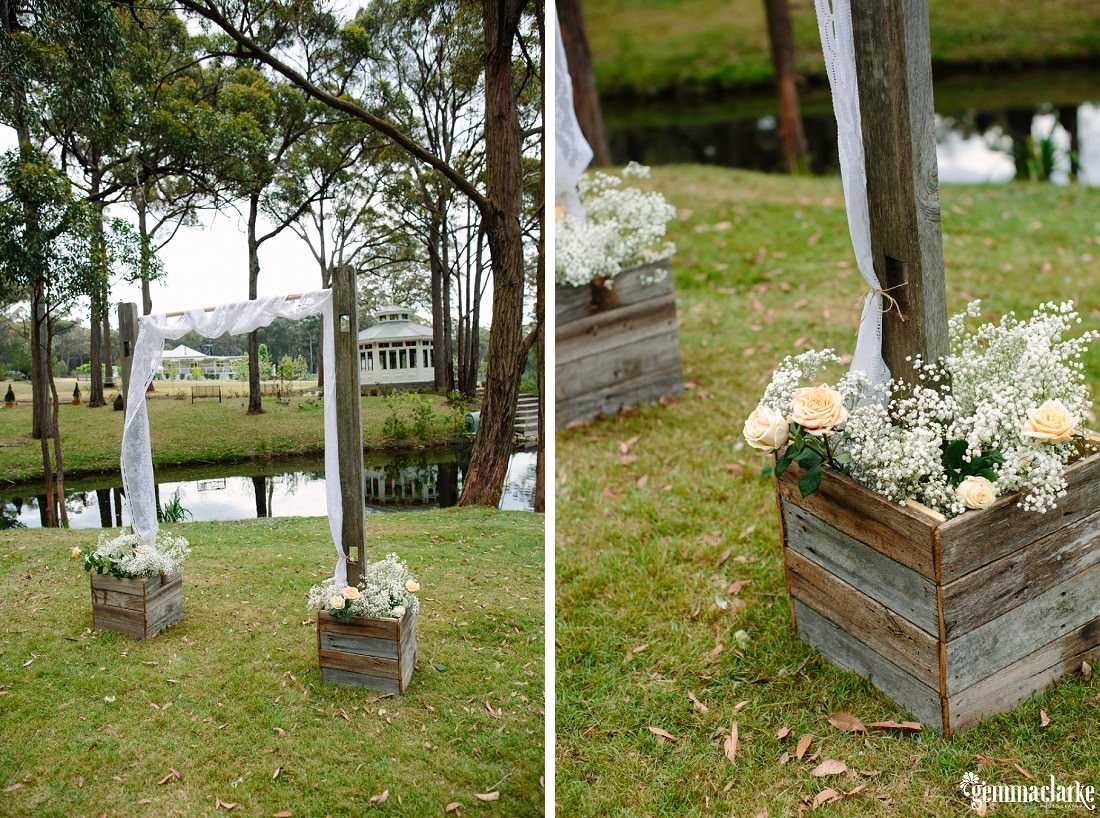 "A wedding arch with white fabric ""planted"" in two wooden crates with white and beige flowers near a small lake"