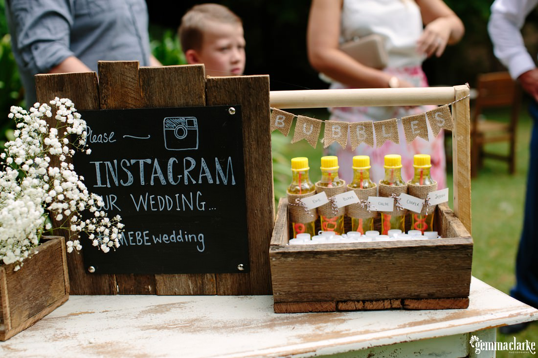 A chalk drawn Instagram sign and a small wooden crate with bubble blowing apparatus