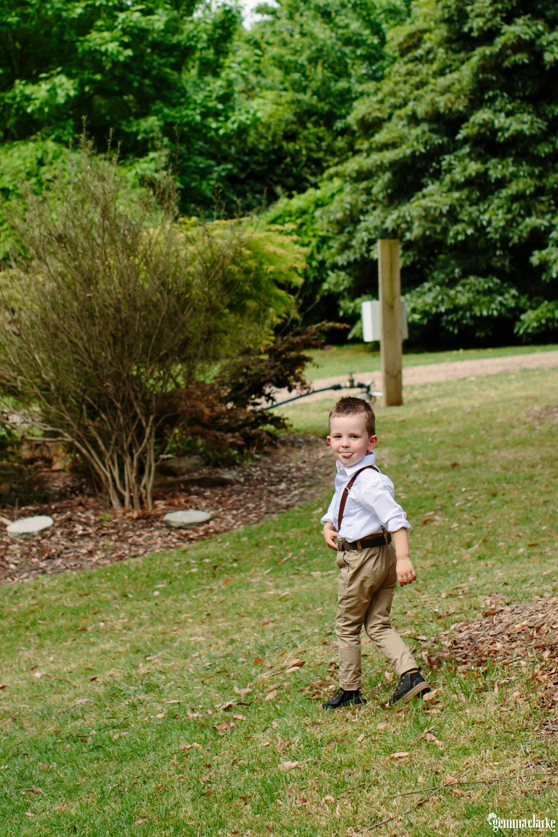 A young boy in a garden walking away, turning back over his shoulder to poke out his tongue