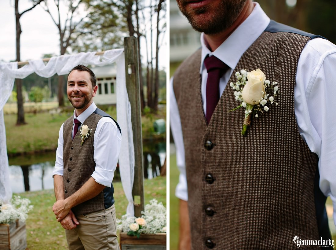 A groom waits for his bride before his wedding ceremony wearing a white shirt, brown tie and vest with a floral buttonhole and tan pants
