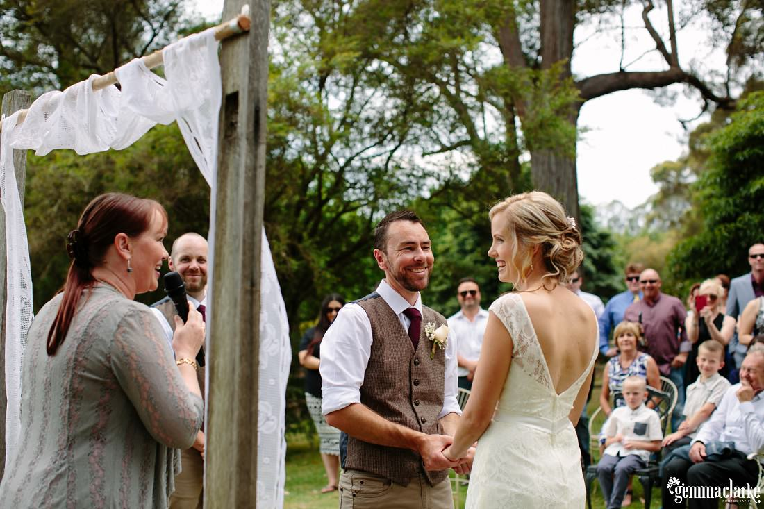 A smiling bride and groom hold hands as their celebrant speaks into a microphone