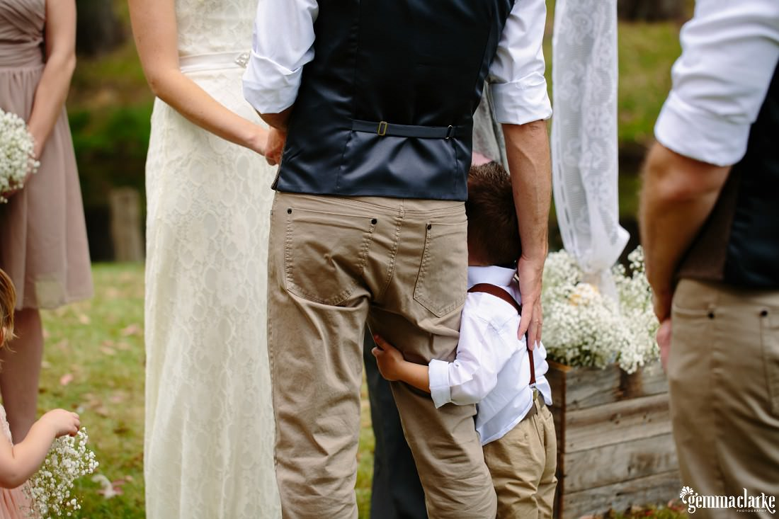 A groom's young son hugs the groom's leg as his father and mother are being married