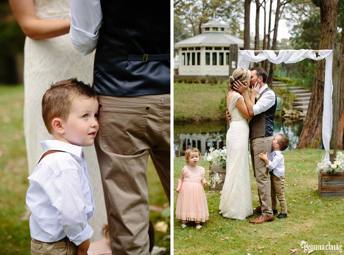 A bride and groom kiss at their ceremony as their young son and daughter stand near