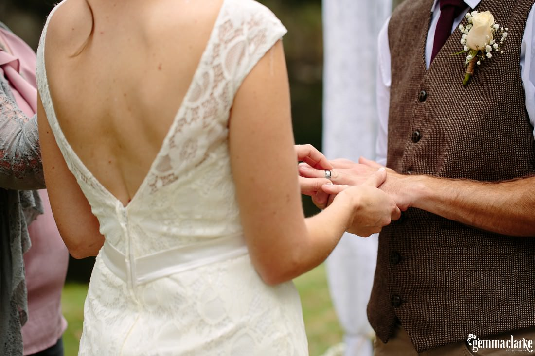 A bride places a wedding ring on her groom's finger