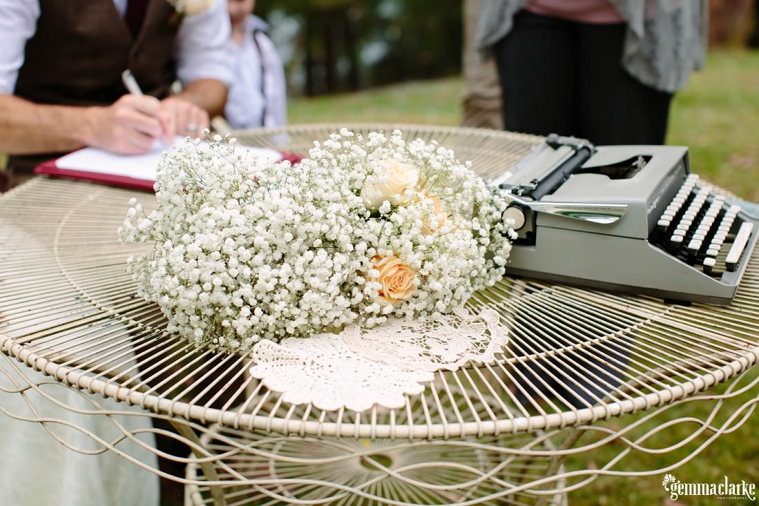 A typewriter and some flowers on the signing table at a wedding ceremony