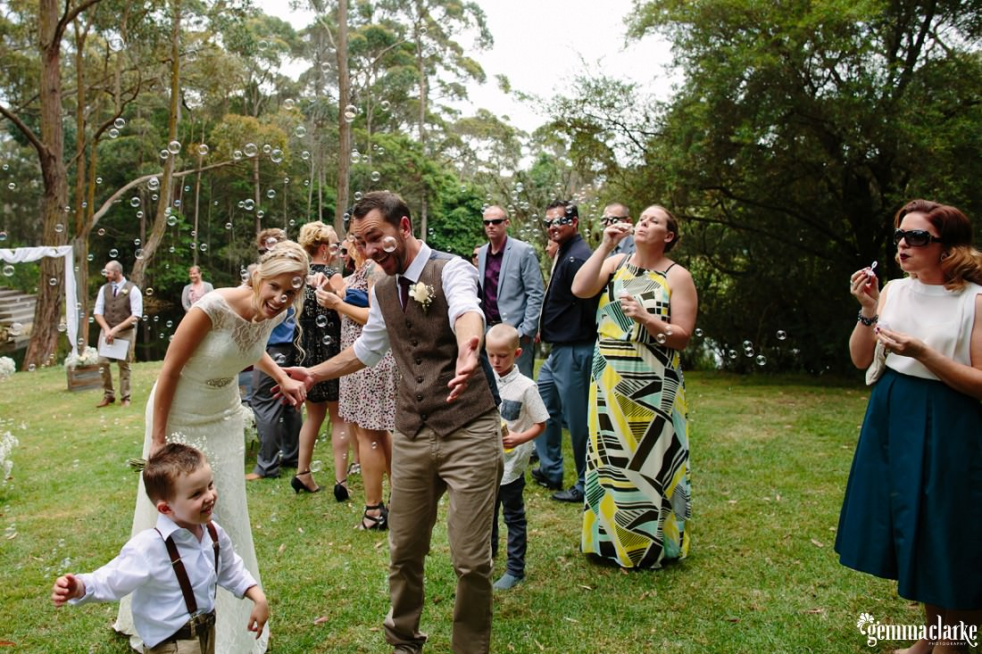 A bride and groom and their young son walk through bubbles being blown by their wedding guests