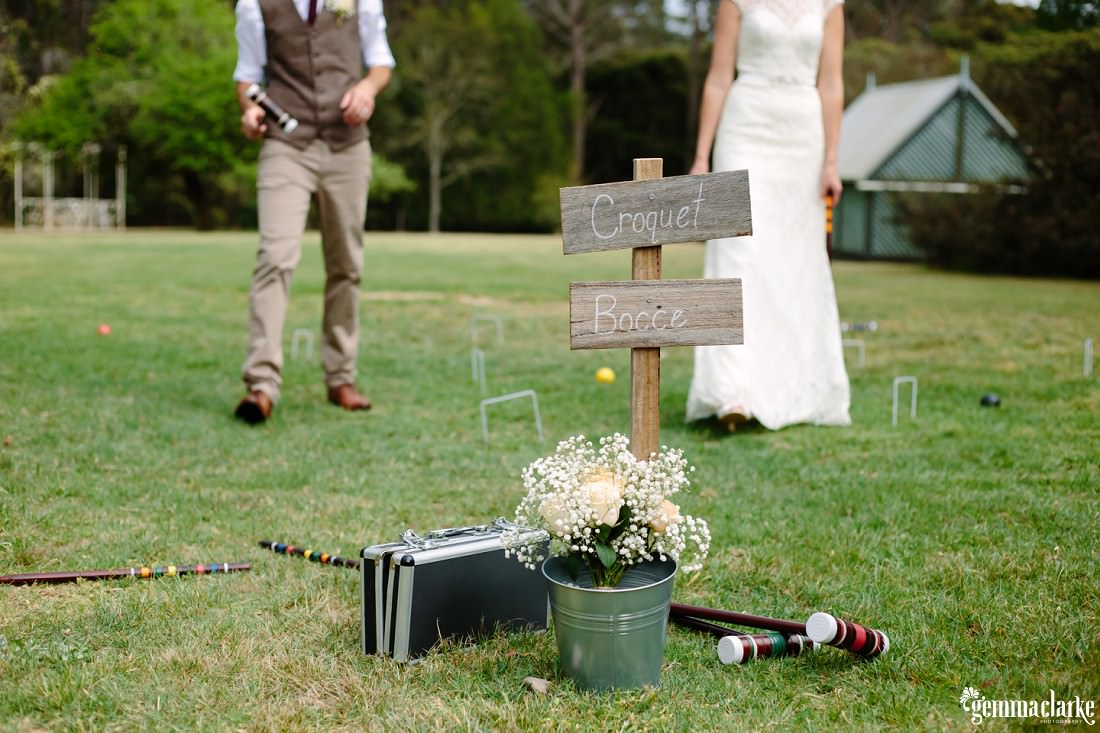 "Croquet sticks and a sign saying ""Croquet, Bocce"", the bride and groom in the background"