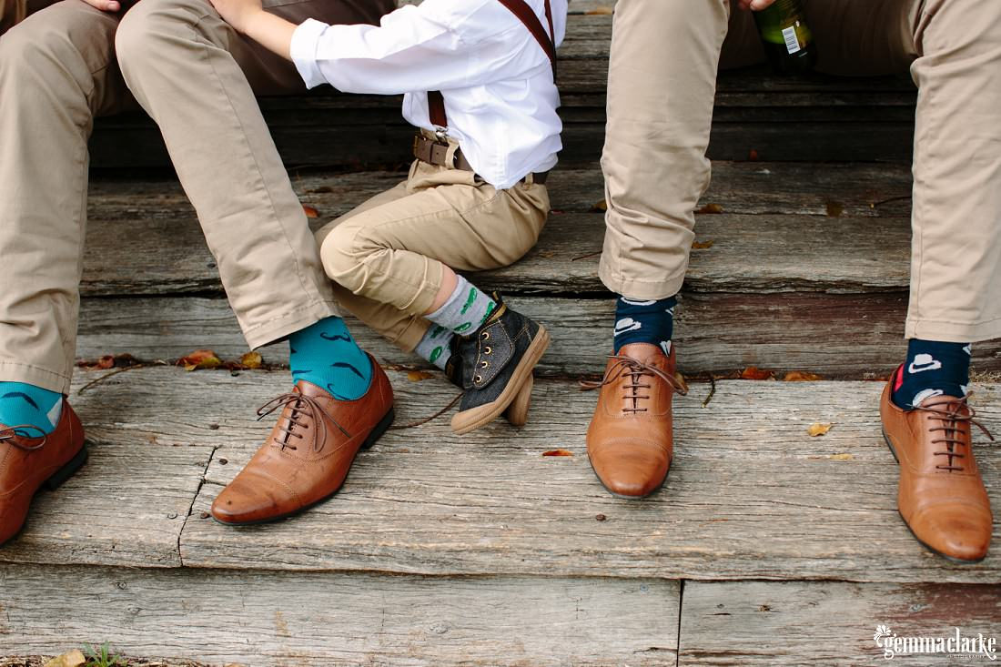 A groom, his son and his best man showing off their shoes and socks