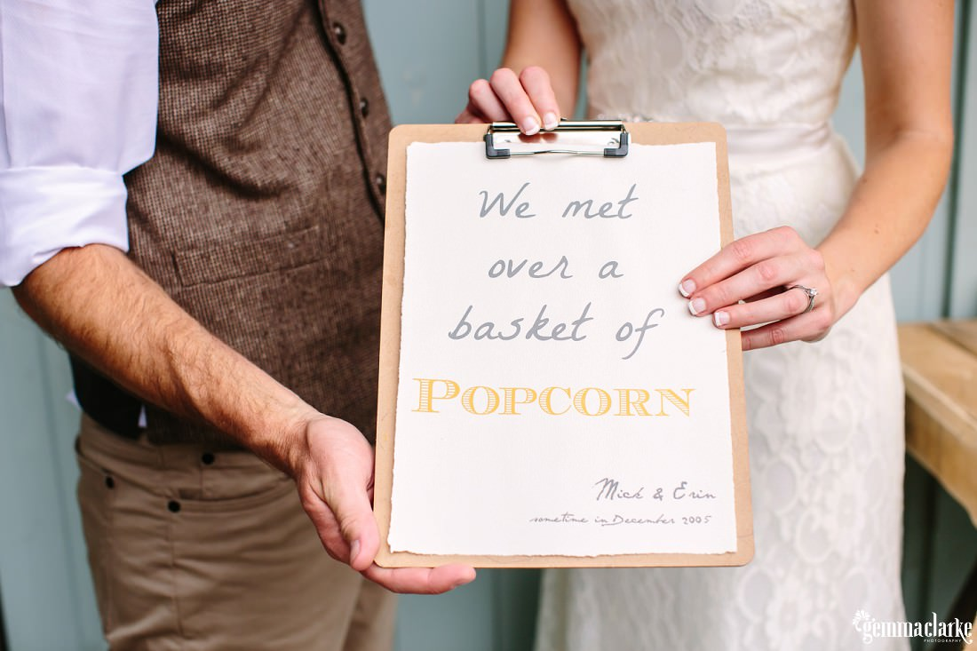 "A bride and groom holding a sign that reads ""We met over a basket of popcorn"""
