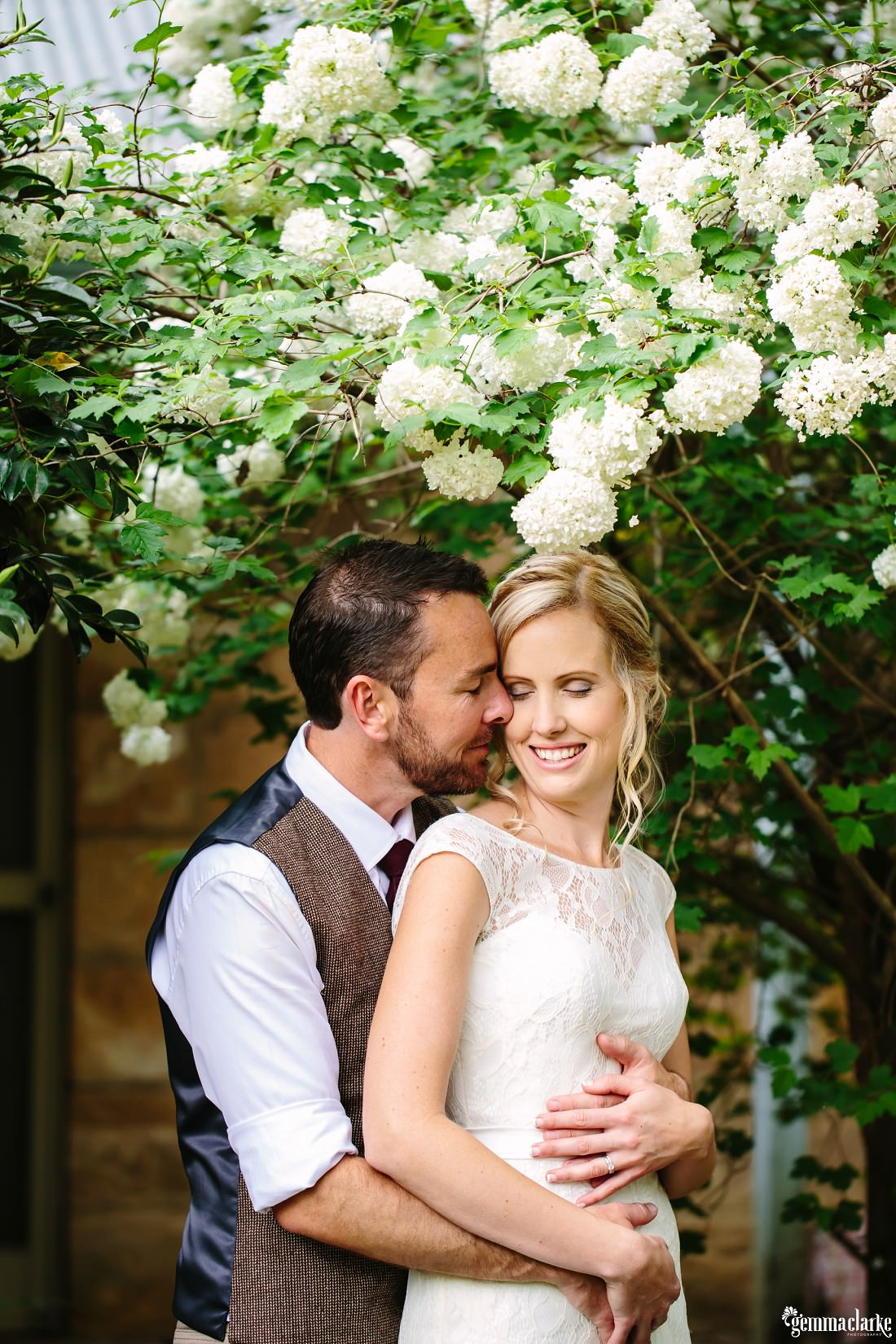 A groom holds his bride close under a tree branch with white flowers