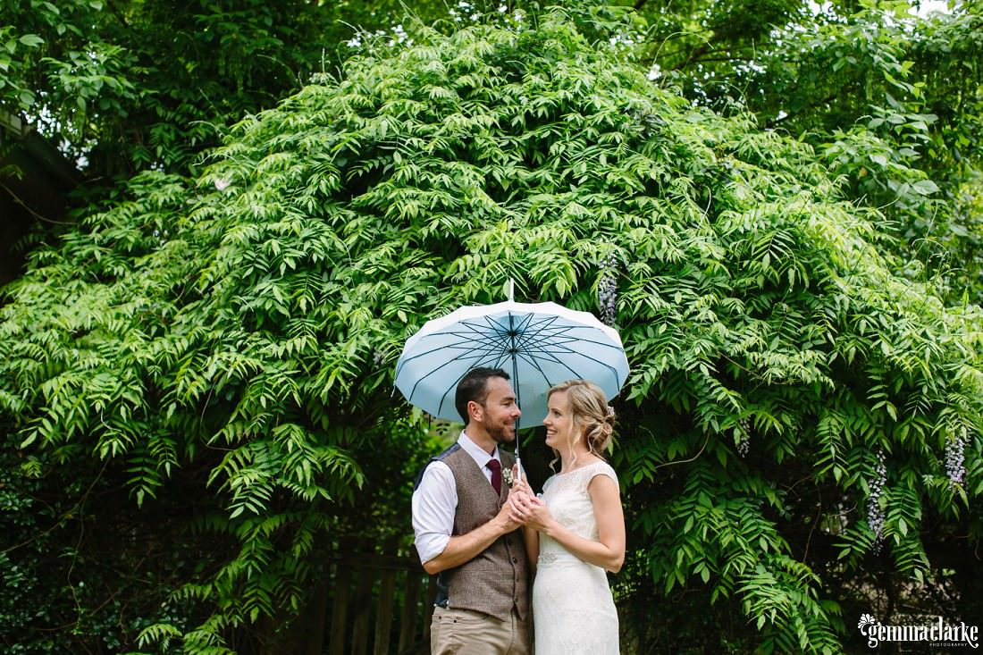 A bride and groom smile at each other underneath a light blue umbrella in front of a large tree