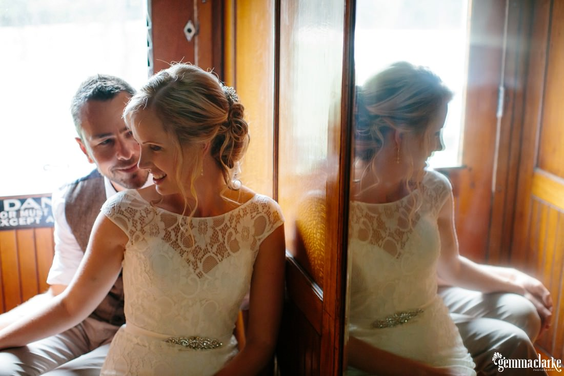 A groom sits close behind his bride with his head over her shoulder