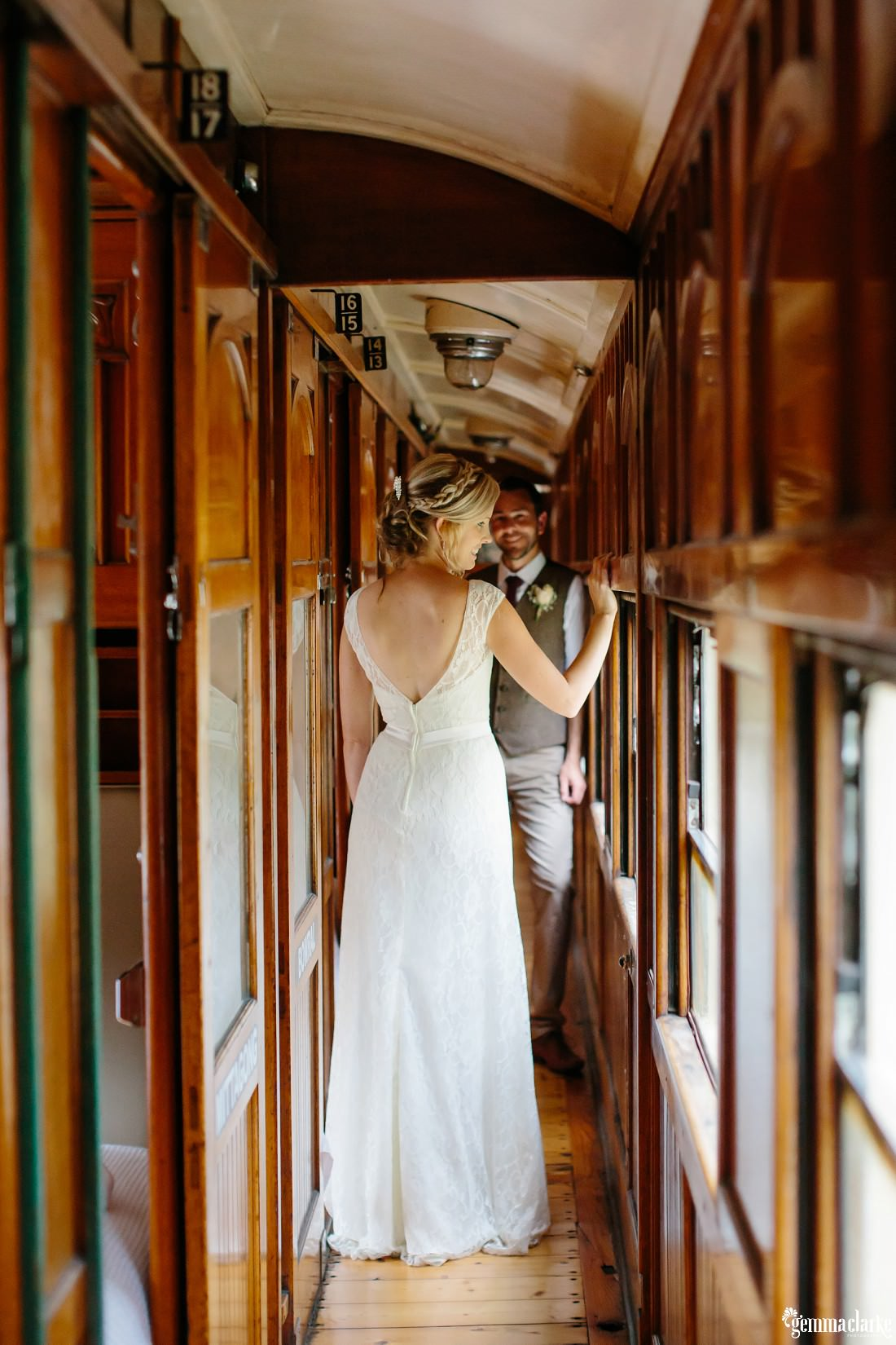 A bride and groom standing together in the corridor of a vintage train carriage