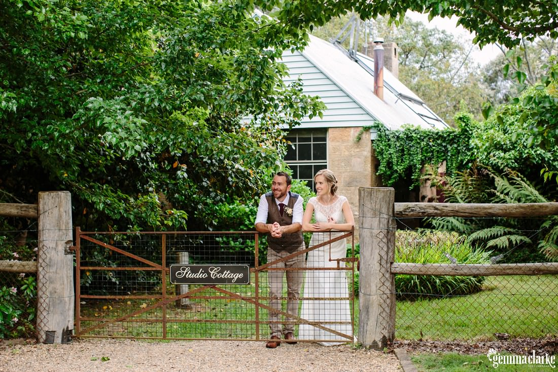 "A bride and groom leaning on an iron gate in a wooden fence with a sign on it saying ""Studio Cottage"", with the cottage in the background"