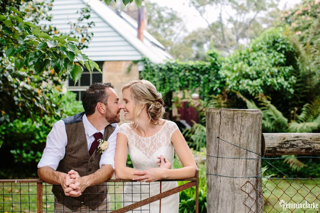 A bride and groom share an eskimo kiss as they lean on a rusty iron gate