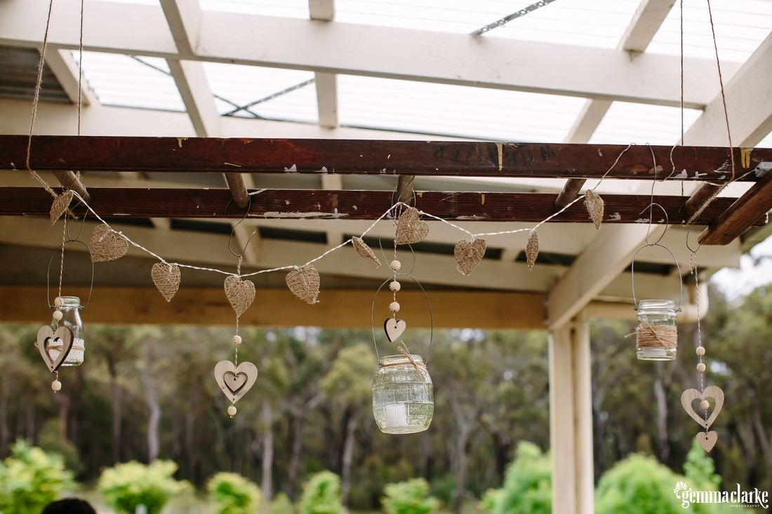 Candles in jars and love heart shaped decorations hanging from a beam